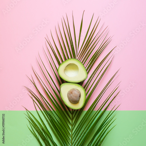 Fototapeta Ripe Avocado on palm leaf on a colored background. Minimal concept