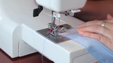 The woman begins to sew on the sewing machine. Women