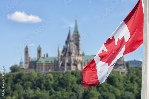 Papiers peints Canada Canadian flag waving with Parliament Buildings hill and Library