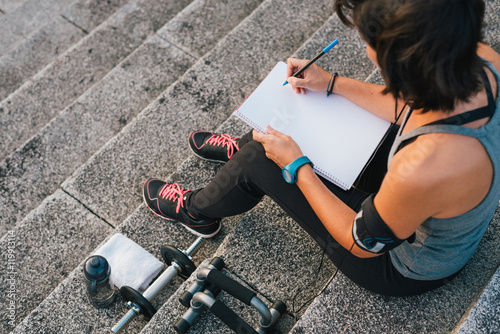 Poster Fitness sporty woman writing on blank notepad while sitting on urban stone stairs before exercises workout routine