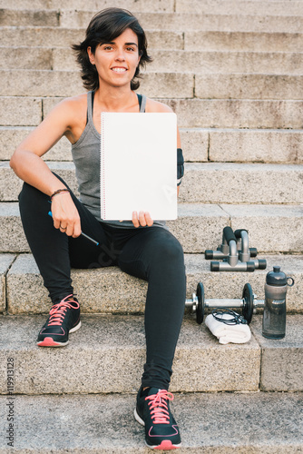 Fitness sporty woman showing blank notepad while sitting on urban stone stairs during exercises workout routine