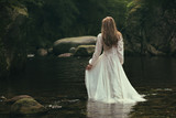 Romantic woman walks into a stream - 119918351