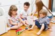 Постер, плакат: quattro bambini giocano in camera con il trenino