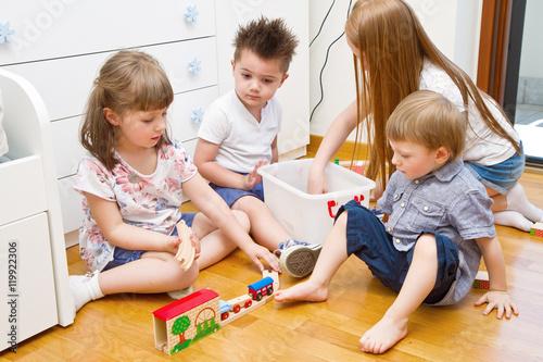quattro bambini giocano in camera con il trenino Poster