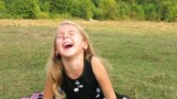 Girl sitting on the grass and bursts out laughing. Irrepressible girls laugh.