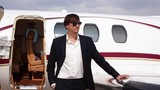 Businessman in Black Suit Stands Beside His Private Jet