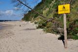 Piaszczysty, osuwający się klif bałtycki - tabliczka z ostrzeżeniem.