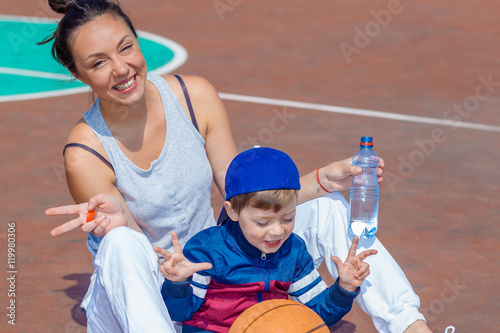 Poster Mom and young son are resting on the basketball field and drinking water