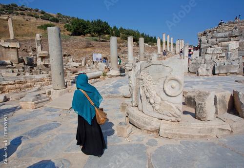 Lady in muslim scarf walking through ruined alley of Greek-Roman city Ephesus
