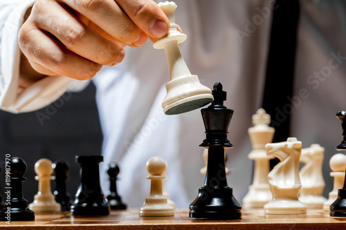 Fotografiet Hand of businessman playing chess