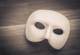 White mask in close up on wooden table. Still life of theatre, carnival or masquerade. Can also be a concept for hiding behind a disguise, a mystery or a tragedy.