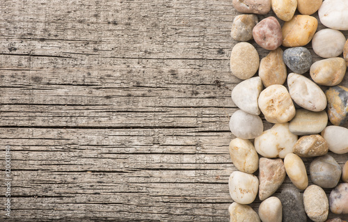 Stones on wooden background, concept of harmony and tranquility. Decoration with stone pebbles as natural design backdrop with copy space.