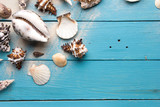 Marine summer postcard. Seashells on blue wooden boards in the sand on the beach - 120028946