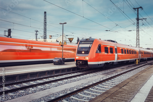 Plakát Modern high speed red passenger commuter trains at the railway platform at sunset with vintage toning