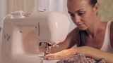 Young woman sews on the sewing machine
