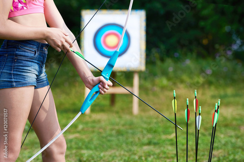 Poster Girl teenager with bow and arrows on background of target