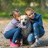 Two little girls with a dog.