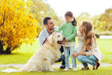 happy family with labrador retriever dog in park