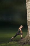 mooie jonge vrouw doet stretch oefeningen buiten in het park, vervaagde achtergrond voor copy-space