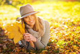 Fototapety Beautiful happy young woman in gray in park in autumn holding leaves