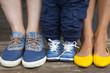 Постер, плакат: Семья: ноги маленького мальчика в джинсовых кроссовках ноги папы в джинсовых кедах и ноги мамы в желтых туфлях балетках