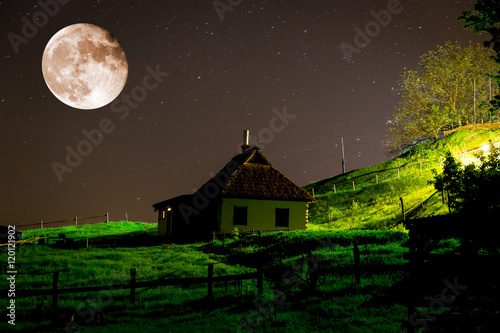 Plagát ukrainian house in village under night sky and big moon