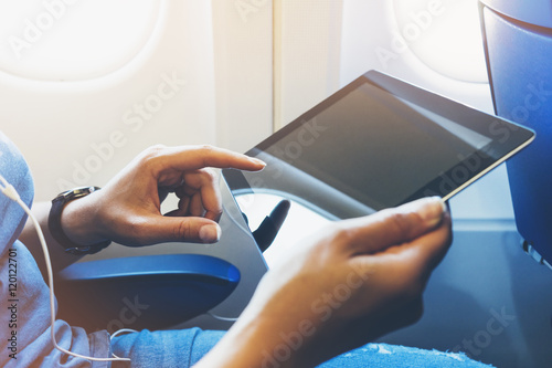 Side view of passenger traveler tourist using tablet at salon airplane. Female hands texting on gadget on background window aircraft, traveler trip concept, mockup blank screen computer with flare