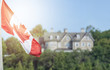 Canadian flag waving over 24 Sussex drive in blurred background
