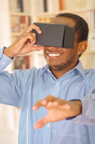 Man wearing blue shirt testing vitrual reality mobile device, holding glasses in front of eyes and smiling