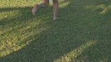 Barefoot young girl running across a lawn