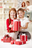 Portrait of two cute little children among gift boxes looking at camera and smiling