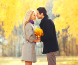 Portrait young loving couple kissing with yellow maple leafs in
