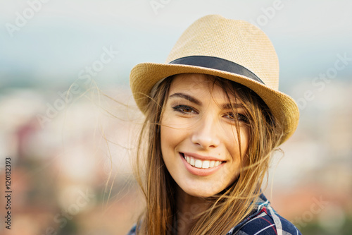 Closeup portrait of beautiful young blonde woman in brown fedora on windy autumn day