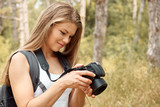 Young female photographer looking at camera screen, walking in the forest. Concept of tourism, hobby and lifestyle.