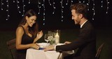 Gorgeous young woman opening a surprise gift from a young man during a romantic dinner for two at a restaurant