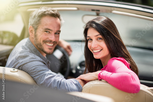 looking at camera a cheerful couple in their convertible car