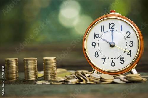 Budzik i pieniądze monety - czas jest pieniądze pojęciem