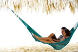 This young couple relax In a hammock on vacation, under a palapa, cabana on the beach in central america - 120214147