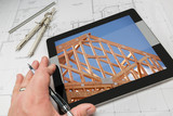 Architect Hand on Tablet Showing Home Framing Over House Plans