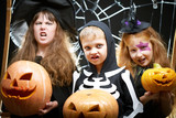 Portrait of three little children with wicked faces holding pumpkins