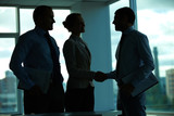 Three business people greeting in office in the dark