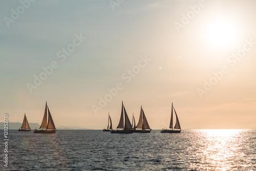Fotobehang Zeilen żeglowanie na morzu podczas zachodu słońca