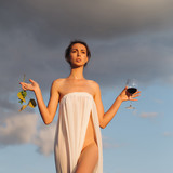 pretty girl with wine glass and grapes over sky