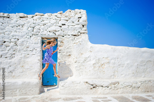 Cute girl in blue dress having fun outdoors near Paraportiani church. Kid at street of typical greek traditional village with white walls and colorful doors on Mykonos Island, in Greece
