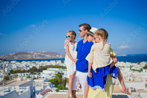 Family vacation in Europe. Parents and kids looking at the cityscape of Mykonos island in Greece © travnikovstudio