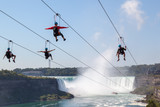 Four unrecognizable people taking zipline ride at Niagara Falls Ontario Canada.  New zipline in Niagara Parks opened in the summer of 2016