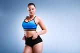Modep plus size is posing in a studio on a blue background in underwear