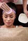 Young beautiful woman receiving facial treatment
