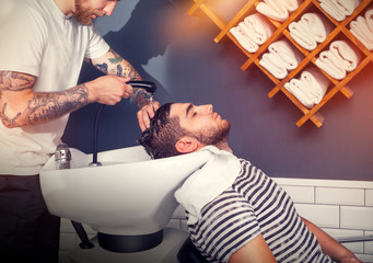 Barber wiping the head of his client with a towel