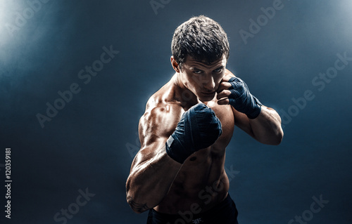 Póster Muscular kickbox or muay thai fighter punching in smoke.